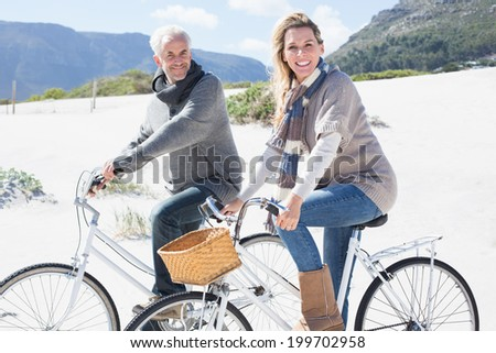 Carefree couple going on a bike ride on the beach smiling at camera on a bright but cool day - stock photo