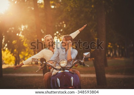 carefree couple having fun riding a scooter together. - stock photo
