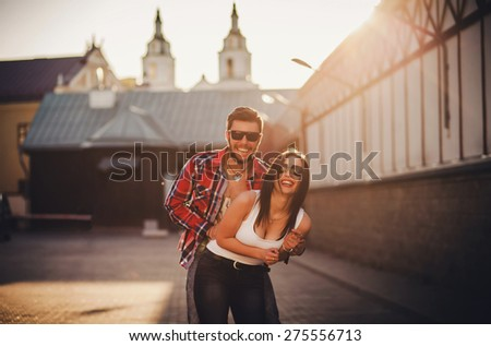 carefree couple is walking around the city and smiles. sunset