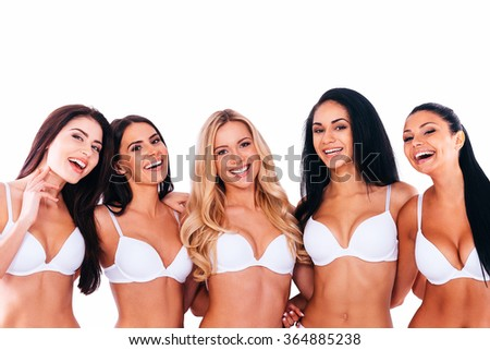 Carefree cuties. Group of cheerful beautiful women in lingerie bonding to each other and smiling while posing against white background - stock photo