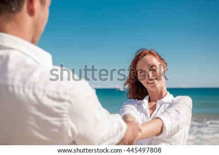 carefree dancing couple on the beach - stock photo
