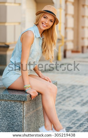 Carefree day in city. Joyful young woman looking at camera and smiling while sitting outdoors - stock photo