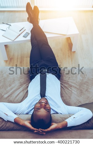 Carefree daydreamer. Top view of happy young African man in formalwear lying on the couch with his legs on a desk and hands behind head - stock photo