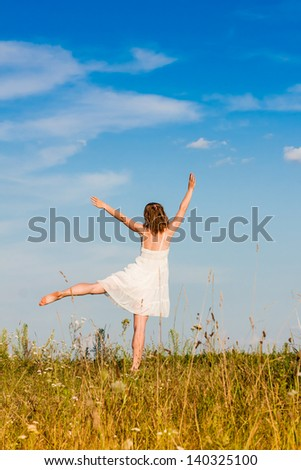 Carefree emotional girl with arms out in field. Summer