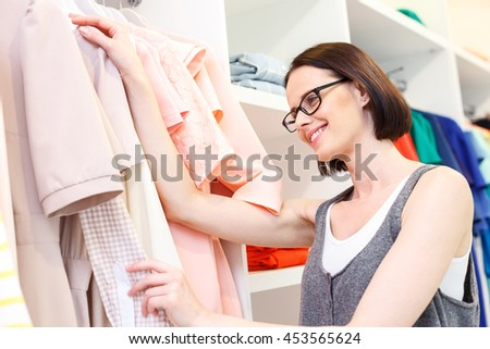 Carefree female customer choosing cloth in shop - stock photo