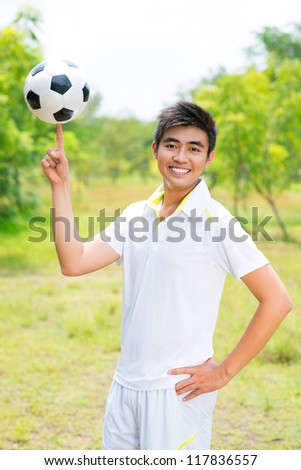 Carefree football player holding the ball on his fingertip