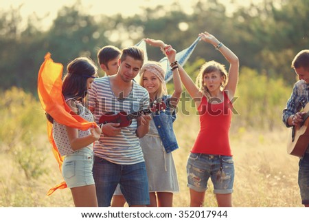 Carefree friends with guitars have fun, outdoors - stock photo