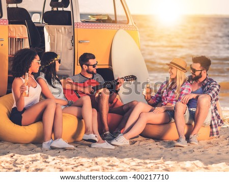 Carefree fun. Group of joyful young people drinking beer and playing guitar while sitting on the beach near their retro minivan