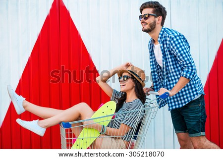 Carefree fun. Side view of cheerful young woman sitting in shopping cart while her boyfriend pushing it - stock photo