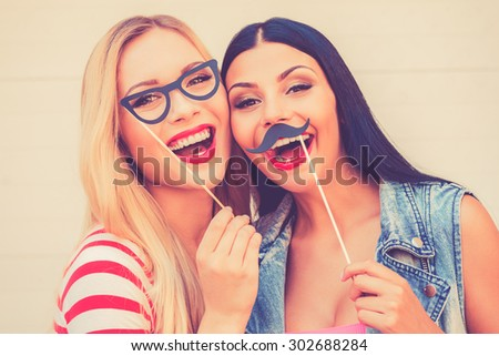Carefree fun. Two cheerful young women making faces while standing outdoors - stock photo