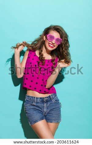 Carefree girl. Beautiful woman in heart shaped glasses holding her hair and smiling. Three quarter length studio shot on teal background. - stock photo