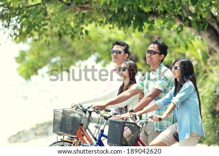 carefree group friends having fun and smiling riding bicycle during the summer day - stock photo