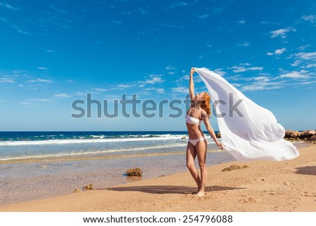 Carefree happy girl on the beach, fit sporty healthy sexy body in bikini, woman enjoys wind, freedom, vacation, summertime fun concept - stock photo