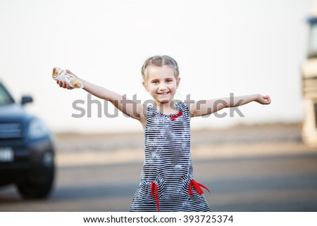 Carefree happy smiling baby girl posing arms to the side and upwards. Outdoors portrait of a child. Selective focus on model. - stock photo