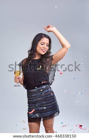 carefree happy woman dancing with arms up at new years eve party while holding a glass of sparkling wine champagne