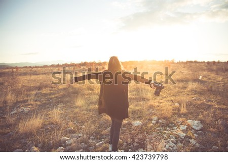 Carefree happy woman  enjoying sun on her face and photographing sunset raising hands in sunlight rays,enjoying nature sunset.Freedom.Enjoyment.Relaxing in meadow at sunrise.Daydreaming - stock photo