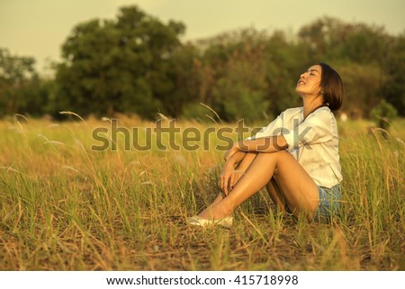 Carefree happy woman lying on green grass meadow enjoying sun on her face.Enjoying nature sunset.Freedom.Enjoyment.Relaxing in mountains at sunrise.Sunshine.Daydreaming - stock photo
