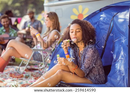 Carefree hipster blowing bubbles in tent at a music festival - stock photo