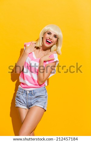 Carefree laughing beautiful blond young woman. Three quarter length studio shot on yellow background. - stock photo