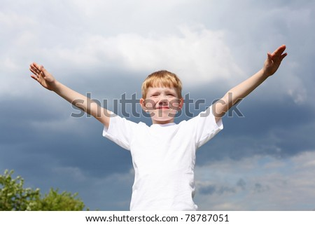 carefree litlle boy outdoors embracing skies on lawn