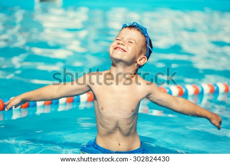 Carefree little caucasian boy spread arms in pool, summer holiday - stock photo