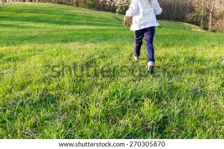 carefree little girl running in the meadow in spring