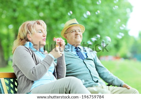 Carefree mature couple blowing bubbles seated on bench in park - stock photo
