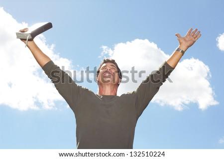 Carefree mature man celebrating success a Bible against cloudy sky. Horizontal Shot. - stock photo