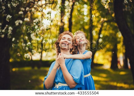 carefree mother and daughter relaxing in the park - stock photo