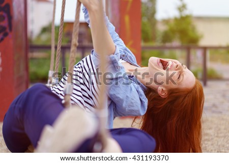 Carefree pretty young redhead woman frolicking in an urban park playing on a rope swing and enjoying a hearty laugh
