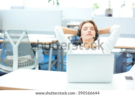Carefree pretty young woman in headset with laptop sitting and relaxing on workplace in office - stock photo