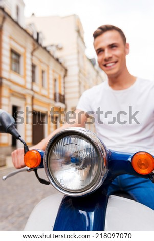 Carefree ride. Happy young man riding scooter along the street and smiling  - stock photo