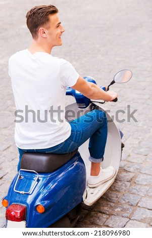 Carefree ride. Rear view of handsome young man in sunglasses riding scooter along the street and smiling  - stock photo