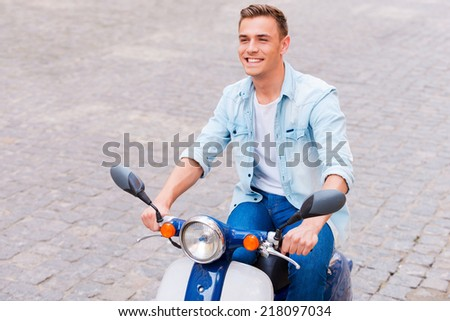 Carefree ride. Top view of handsome young man in sunglasses riding scooter along the street and smiling  - stock photo