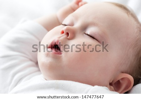 Carefree sleeping little baby on a bed