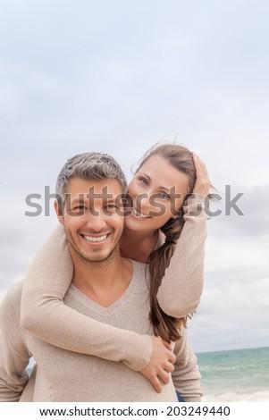 carefree smiling couple at the coast - stock photo