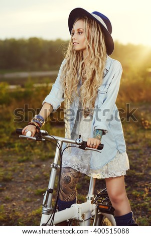 Carefree smiling girl in boho style clothes rides a bicycle. Beauty, fashion. Summertime. - stock photo