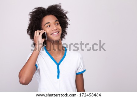 Carefree talk. Cheerful African teenager working on digital tablet and smiling while standing isolated on grey background - stock photo
