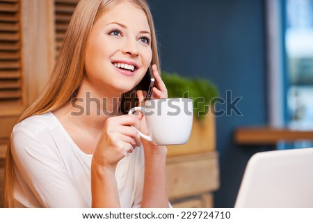 Carefree talk in cafe. Beautiful young smiling woman talking on the mobile phone while enjoying coffee in cafe