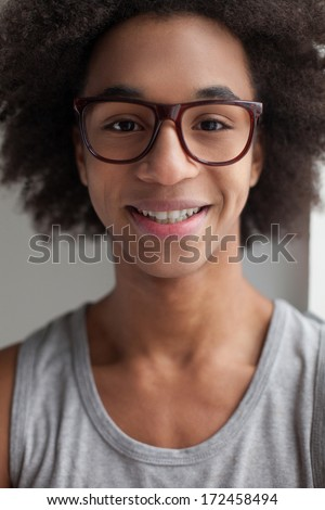 Carefree teenage boy. Cheerful teenage African boy in glasses looking at camera and smiling - stock photo