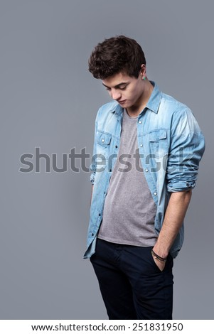 Carefree teenager posing with hands in pockets on gray background - stock photo