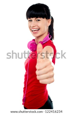 Carefree teenager with headphones flashing thumbs up sign to camera. - stock photo