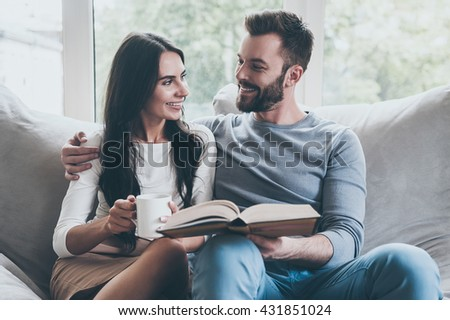 Carefree time together. Beautiful young loving couple looking at each other with smiles while sitting together on the couch  - stock photo