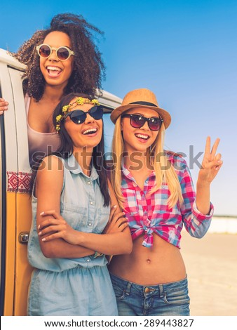 Carefree time with friends. Happy young African woman looking out from the retro minivan while two her friends standing near her
