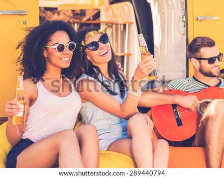 Carefree time with friends. Two cheerful young women holding bottles with beer and smiling while man playing the guitar with minivan in the background - stock photo
