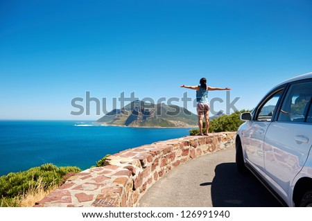 carefree tourist stands on chapmans peak drive with arms outstretched in freedom girl pose with rental car - stock photo