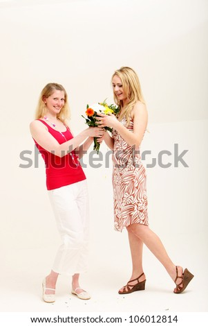 Carefree vivacious woman receiving a gift of a bouquet of flowers from her friend on a white studio background