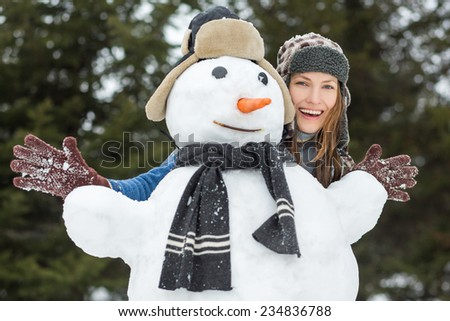 Carefree winter funny young woman with snowman and dark forest on the background - stock photo