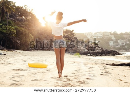 carefree woman dancing in the sunset on the beach. Outdoors lifestyle portrait of girl - stock photo