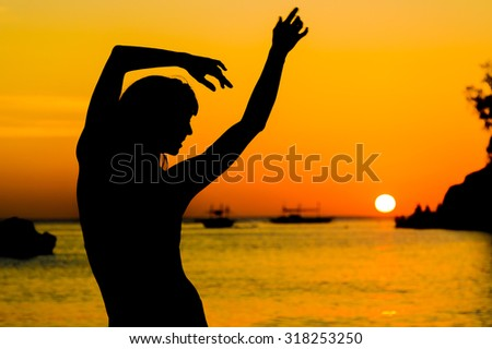 carefree woman dancing in the sunset on the beach. vacation vitality healthy living concept - stock photo